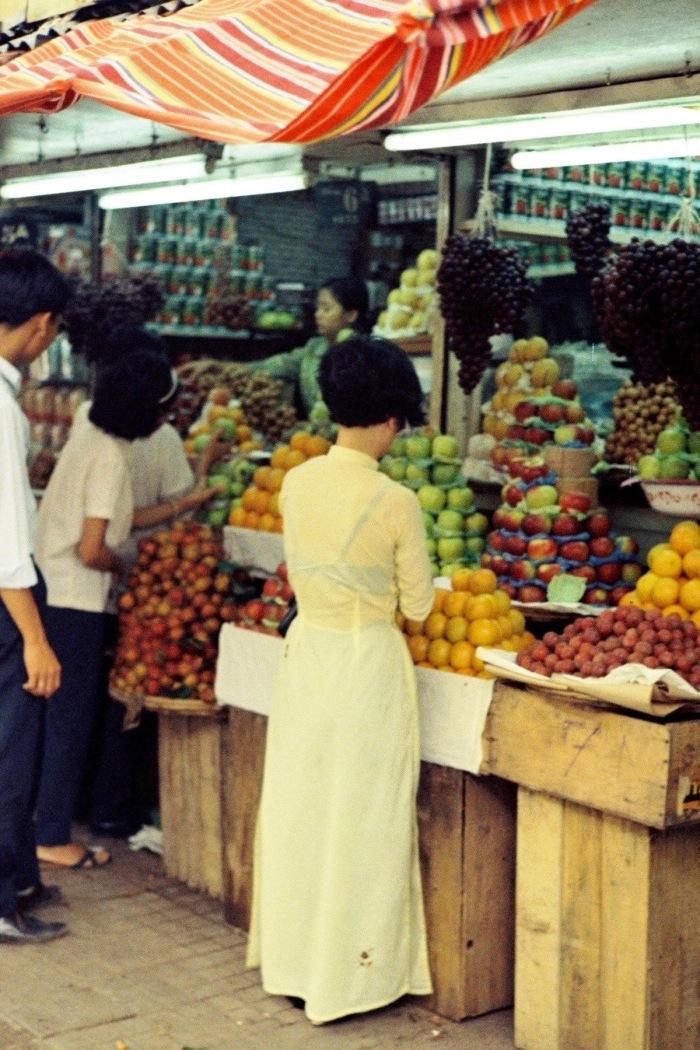 Thiếu nữ áo dài chọn mua hoa quả